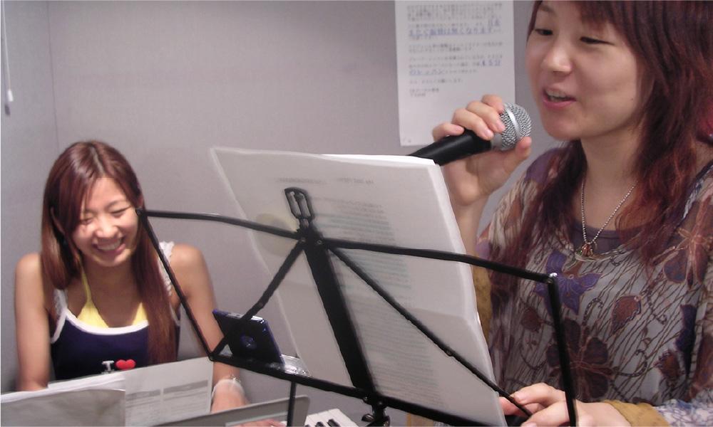 歌う女性と笑顔の講師